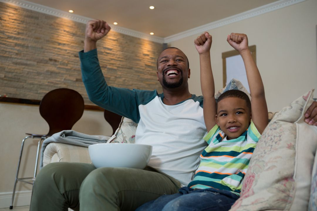 Excited father and son watching football match in living room at home Free Stock Images from PikWizard