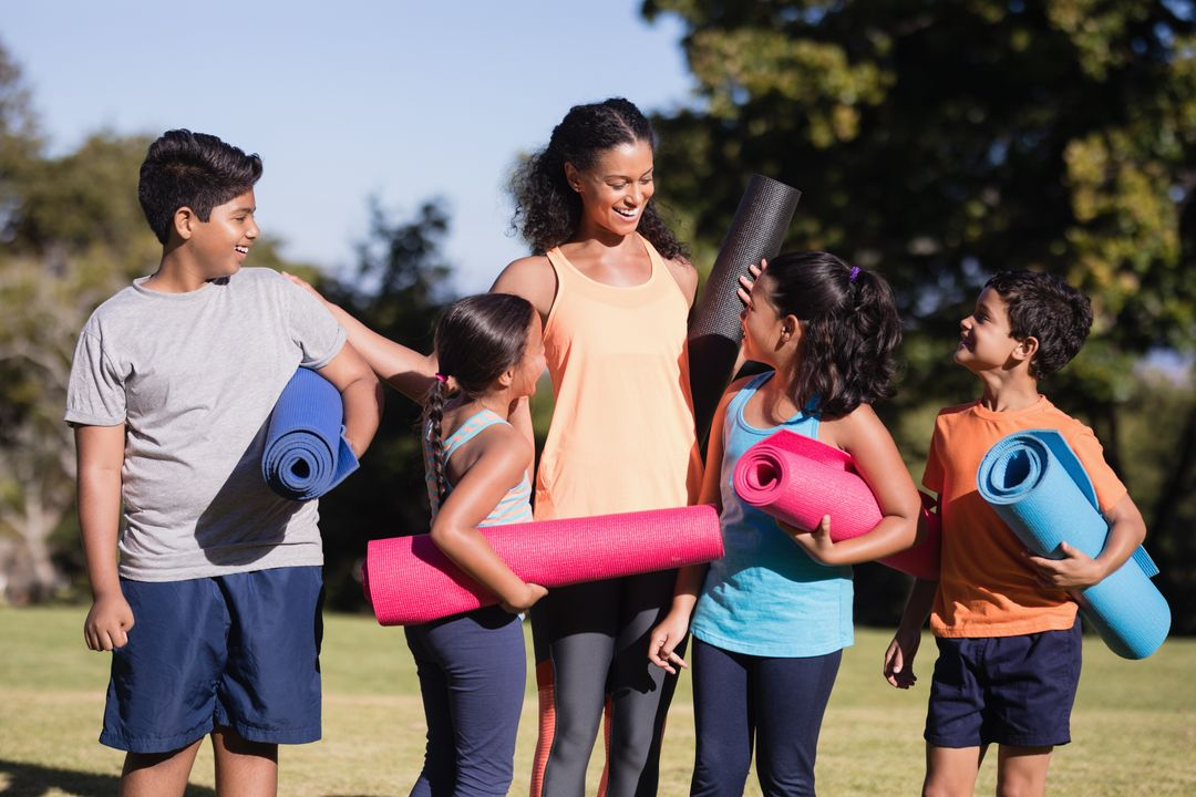 Happy children with female instructor holding exercise mats at park Free Stock Images from PikWizard