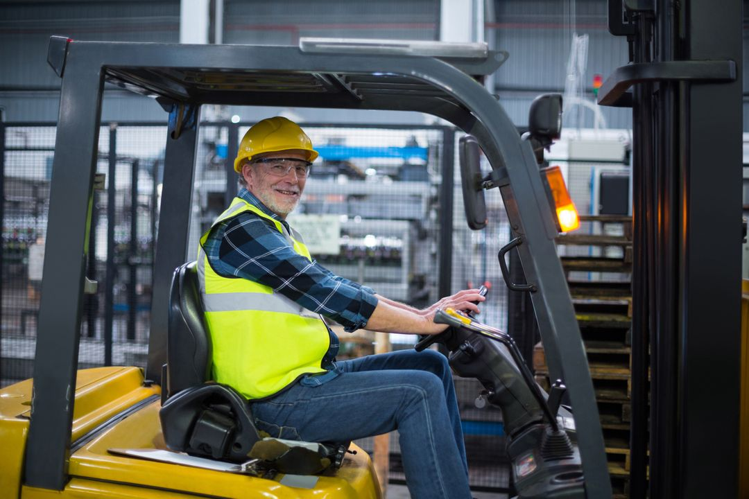 Portrait of smiling factory worker driving forklift in factory Free Stock Images from PikWizard