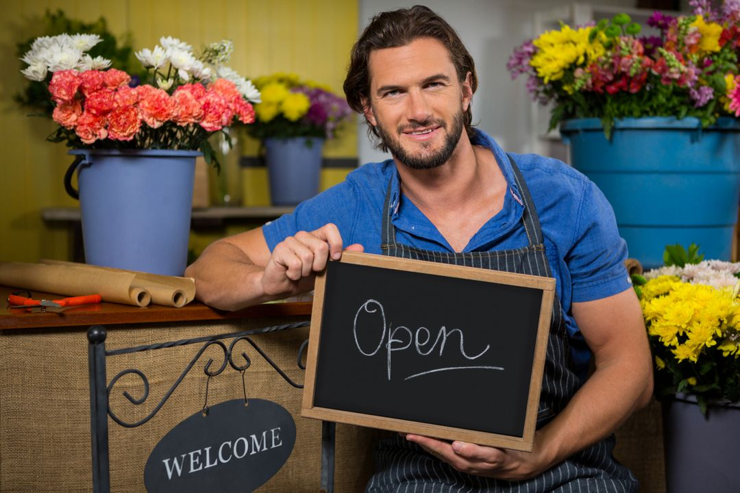 Portrait of male staff holding a board with open sign in flower shop Free Stock Images from PikWizard
