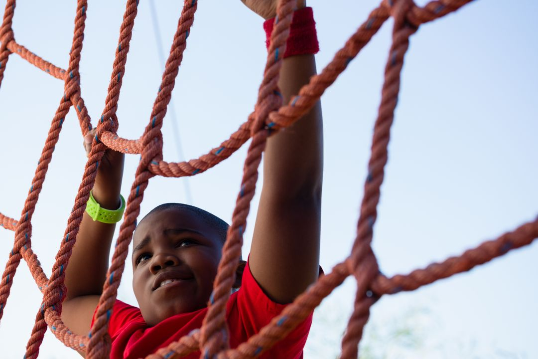 Boy climbing a net during obstacle course training in the boot camp Free Stock Images from PikWizard
