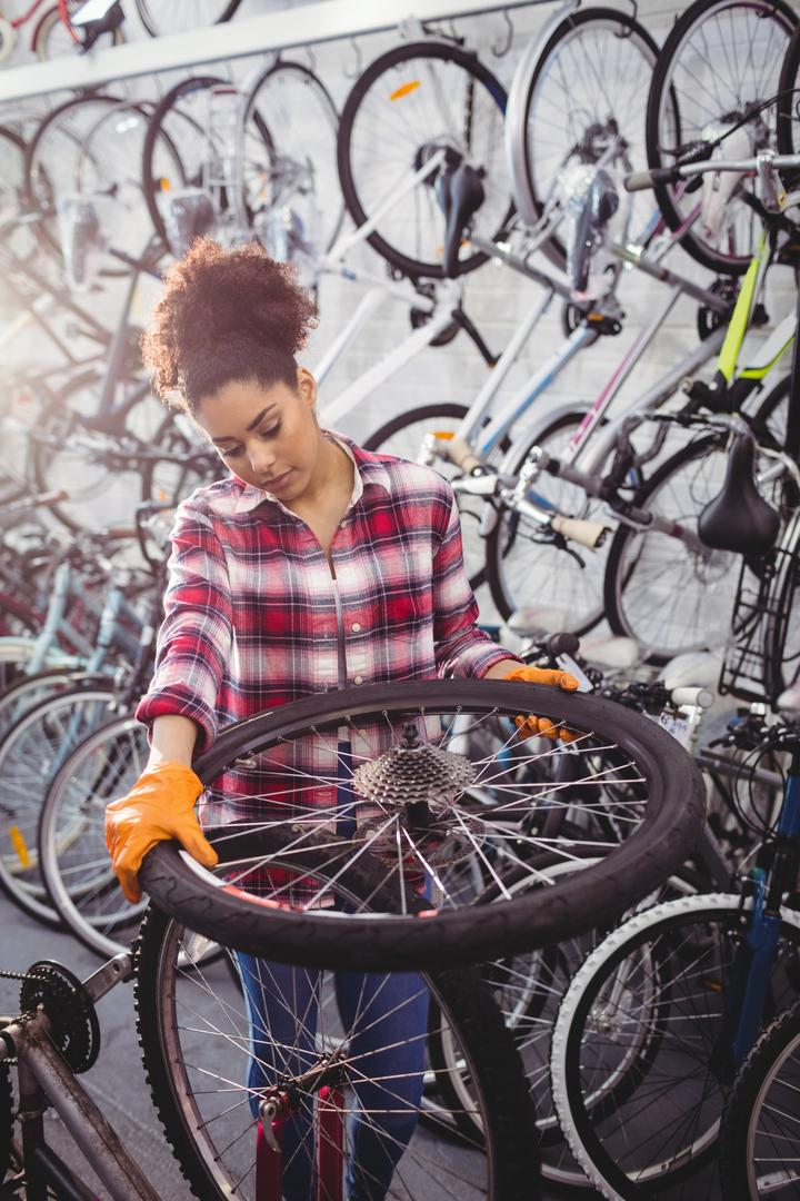 Mechanic examining a bicycle wheel in workshop Free Stock Images from PikWizard