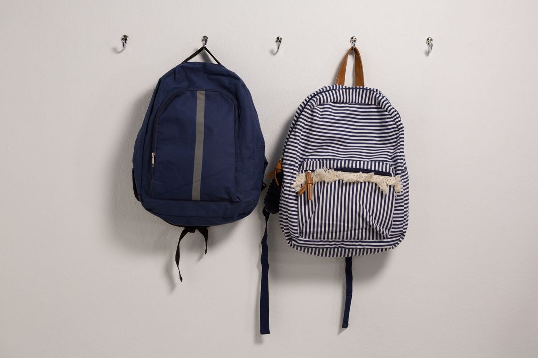 Schoolbags hanging on hook against wall Free Stock Images from PikWizard