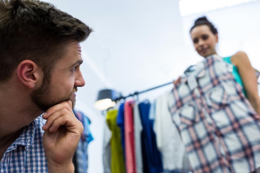 Man looking at woman holding shirt in mall