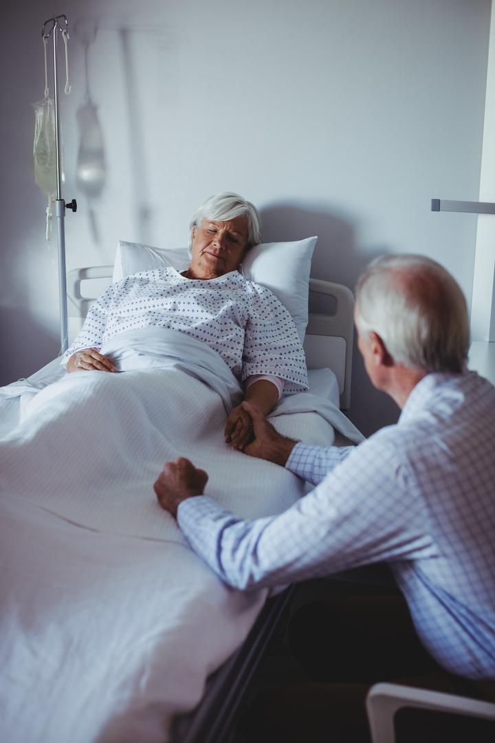 Ill woman sleeping on bed while worried man sitting beside her bed in the hospital