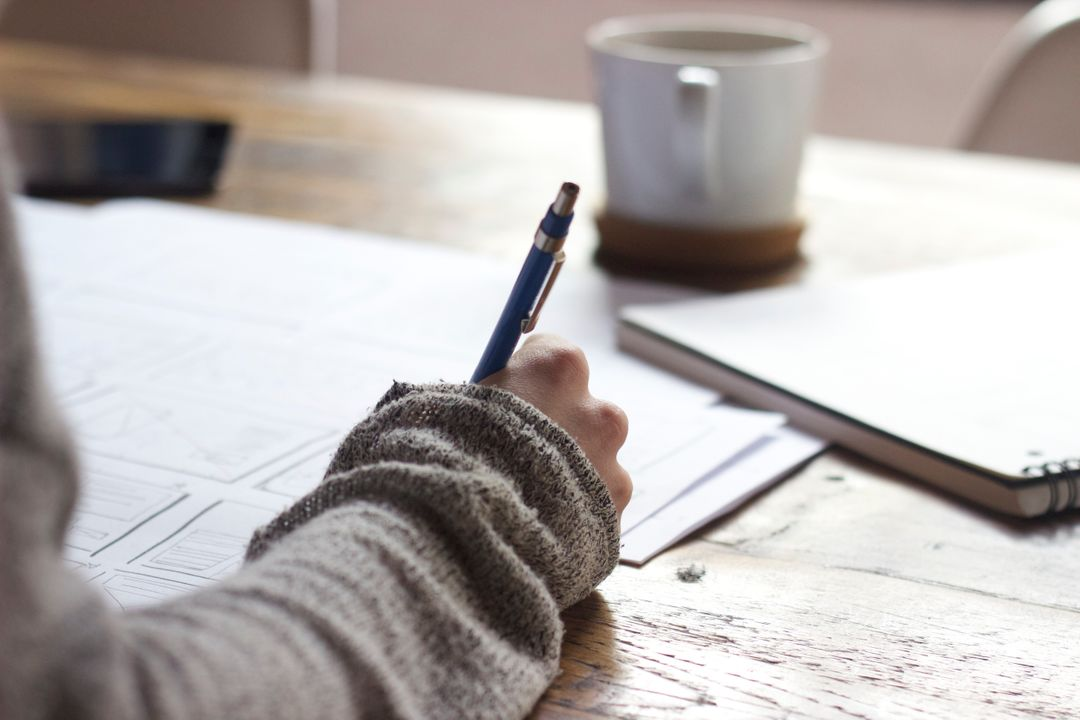 Image of a Person Writing with a Pen