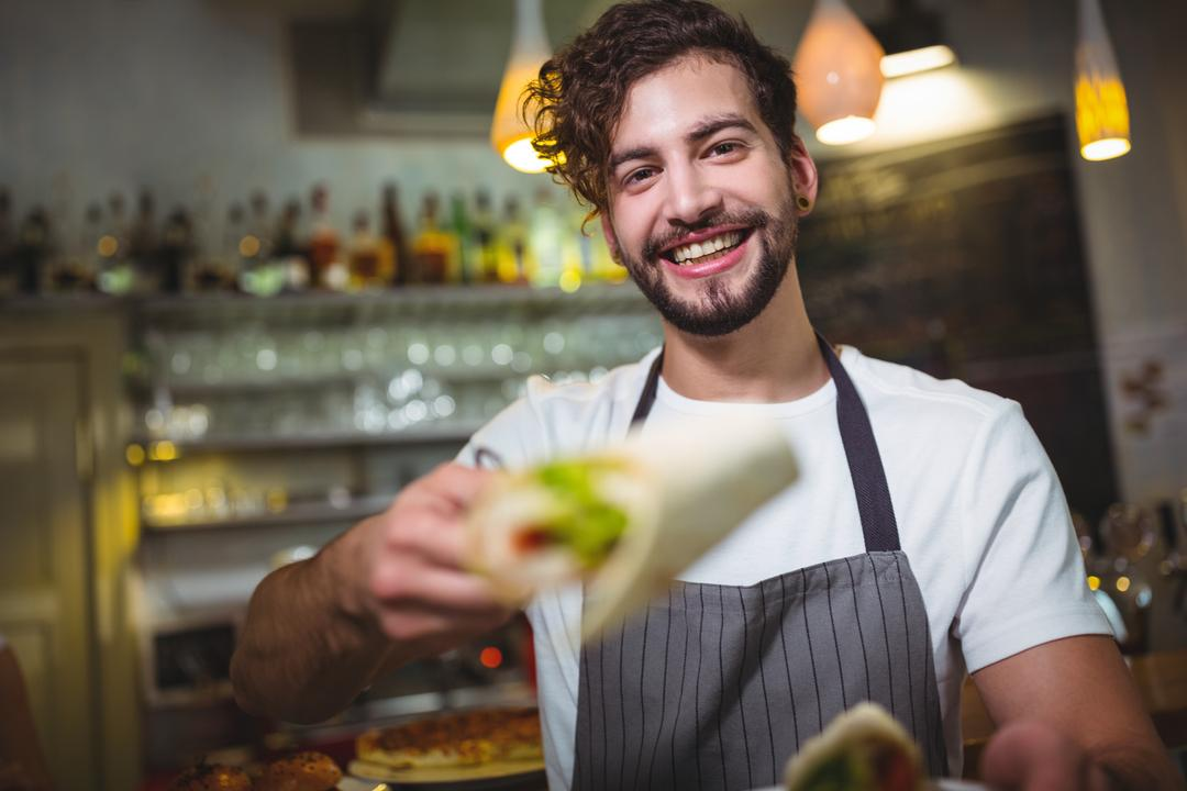 Portrait of waiter holding vegetable roll in café Free Stock Images from PikWizard