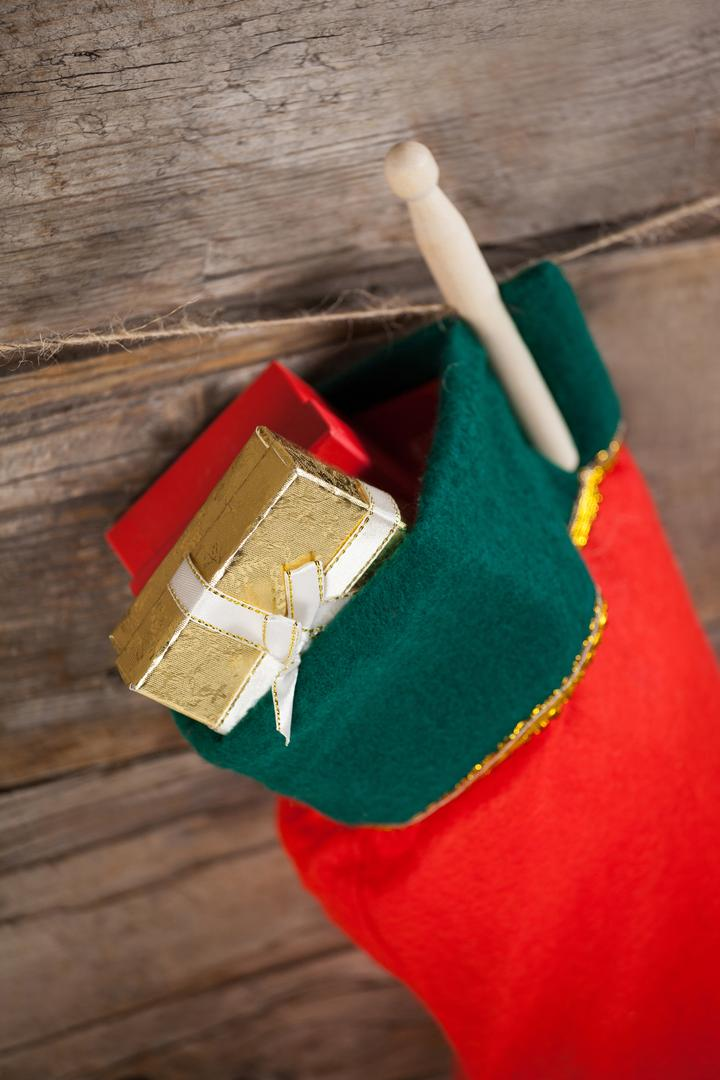 Christmas stocking with present box hanging against wooden wall during christmas time