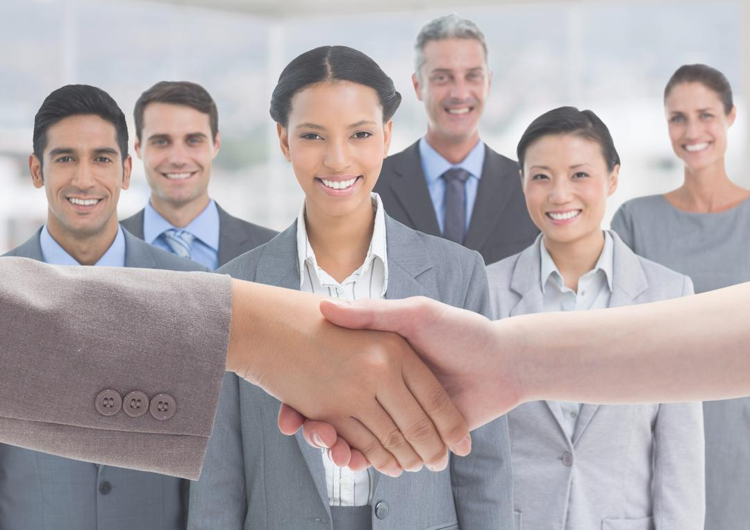 Hand of businesspeople shaking hands with smiling business executives in background