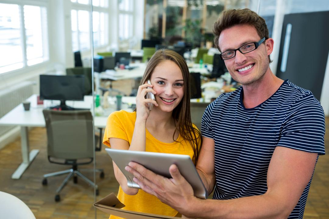 Male and female graphic designers using digital tablet in office