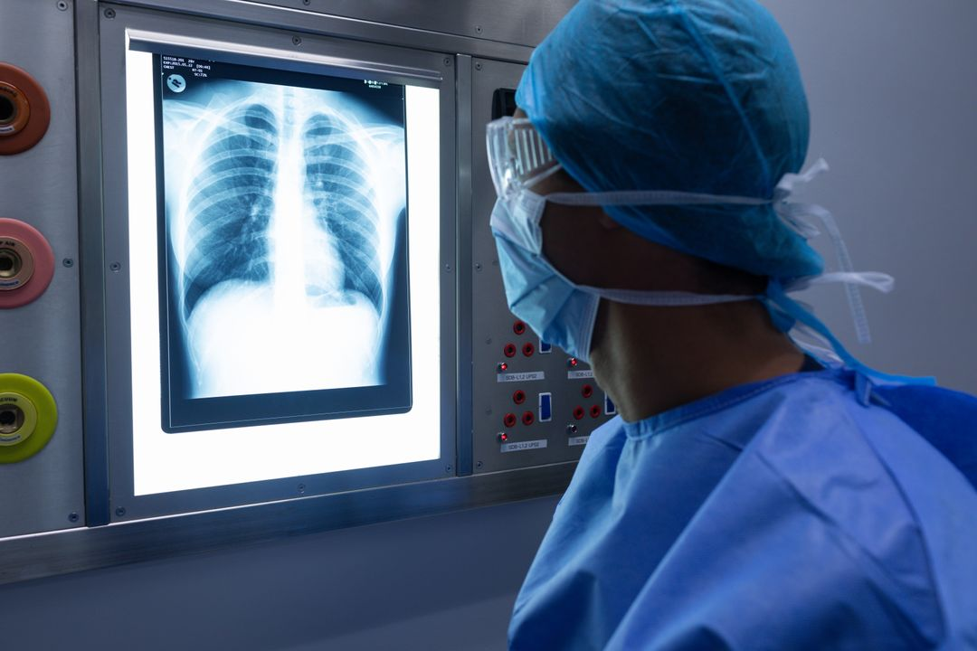Rear view of Caucasian male surgeon examining x-ray on light box in operation theater at hospital