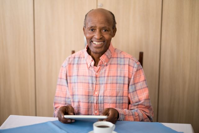 Portrait of smiling senior man sitting with digital tablet at table