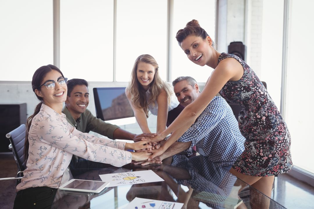 Portrait of smiling business people stacking hands at creative office desk Free Stock Images from PikWizard