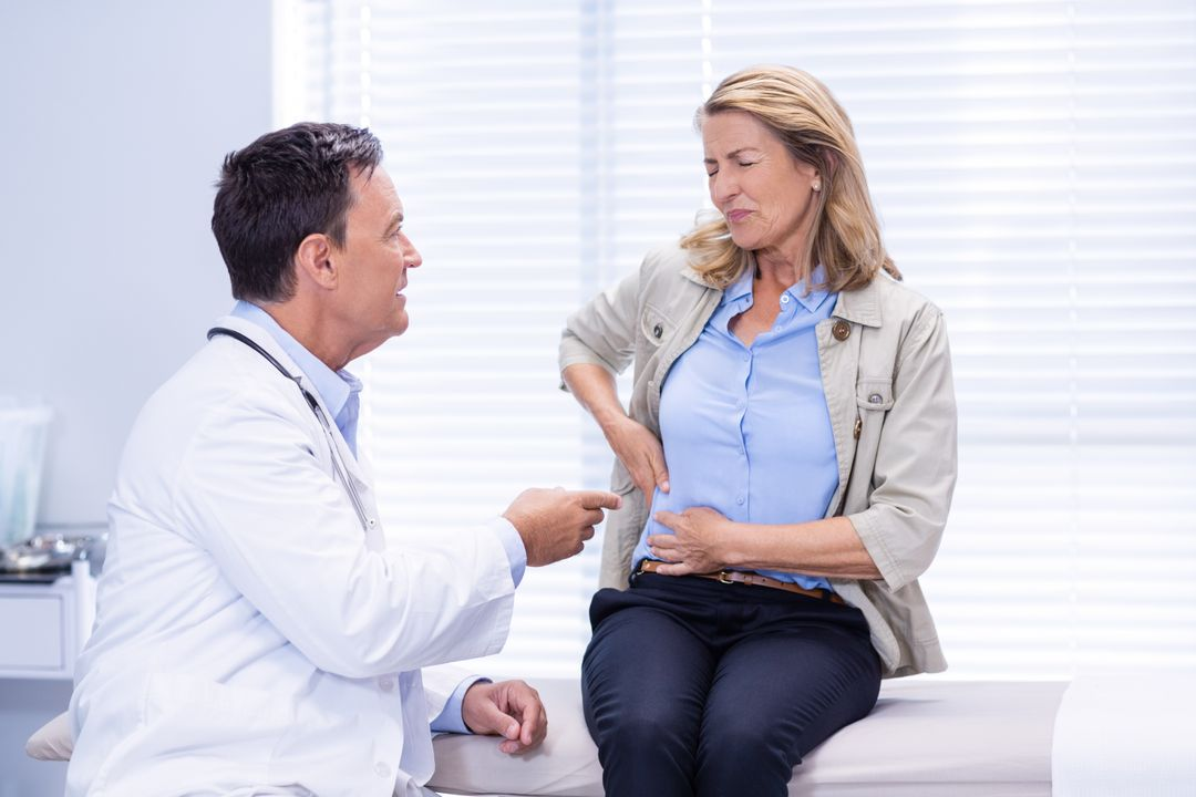 Patient suffering from stomach ache while consulting doctor in clinic Free Stock Images from PikWizard
