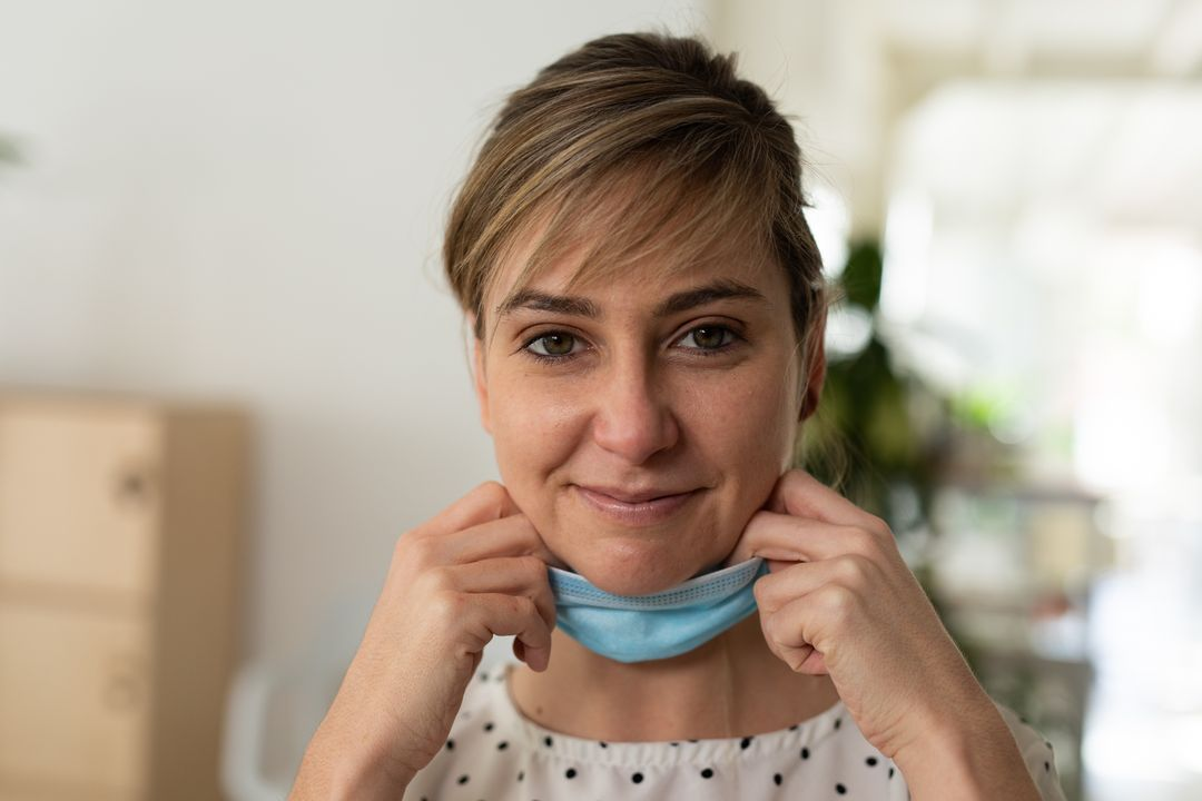 A caucasian woman pulling down her mask showing a smile at an office. She's wearing a white blouse with polka dots. Free Stock Images from PikWizard