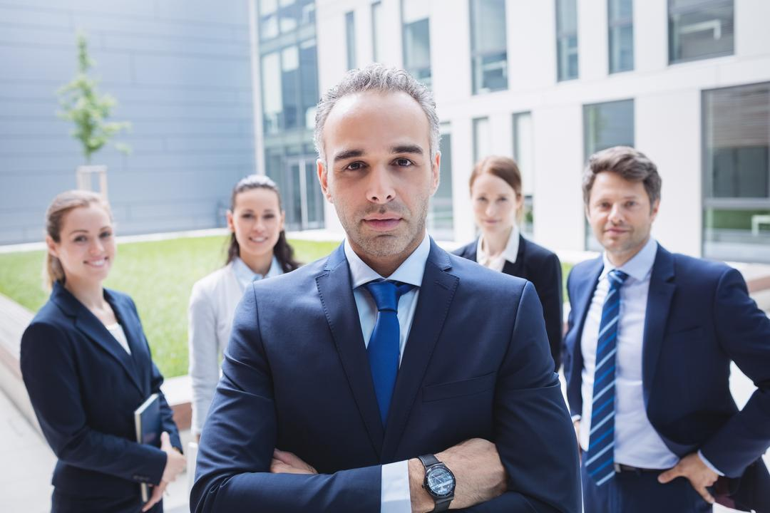 Portrait of confident businessman with colleagues standing outside office building Free Stock Images from PikWizard
