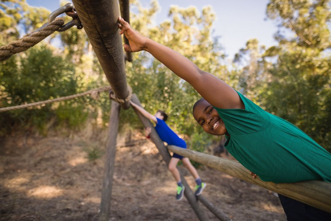 Portrait of happy boy exercising on outdoor equipment during obstacle course in boot camp Free Stock Images from PikWizard