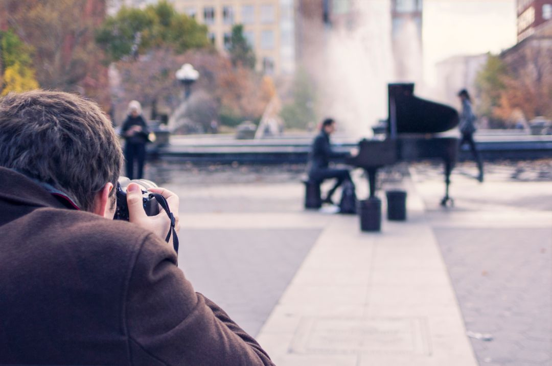 Man taking photo of piano player in a busy outdoor plaza.