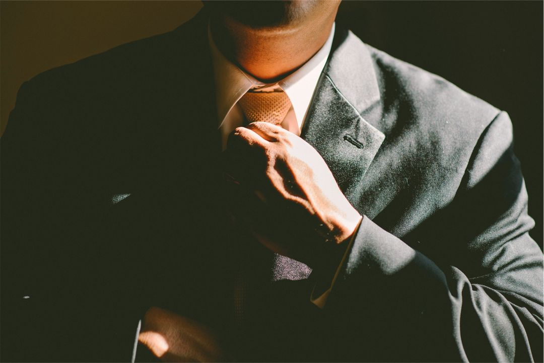Photograph of a man adjusting his tie
