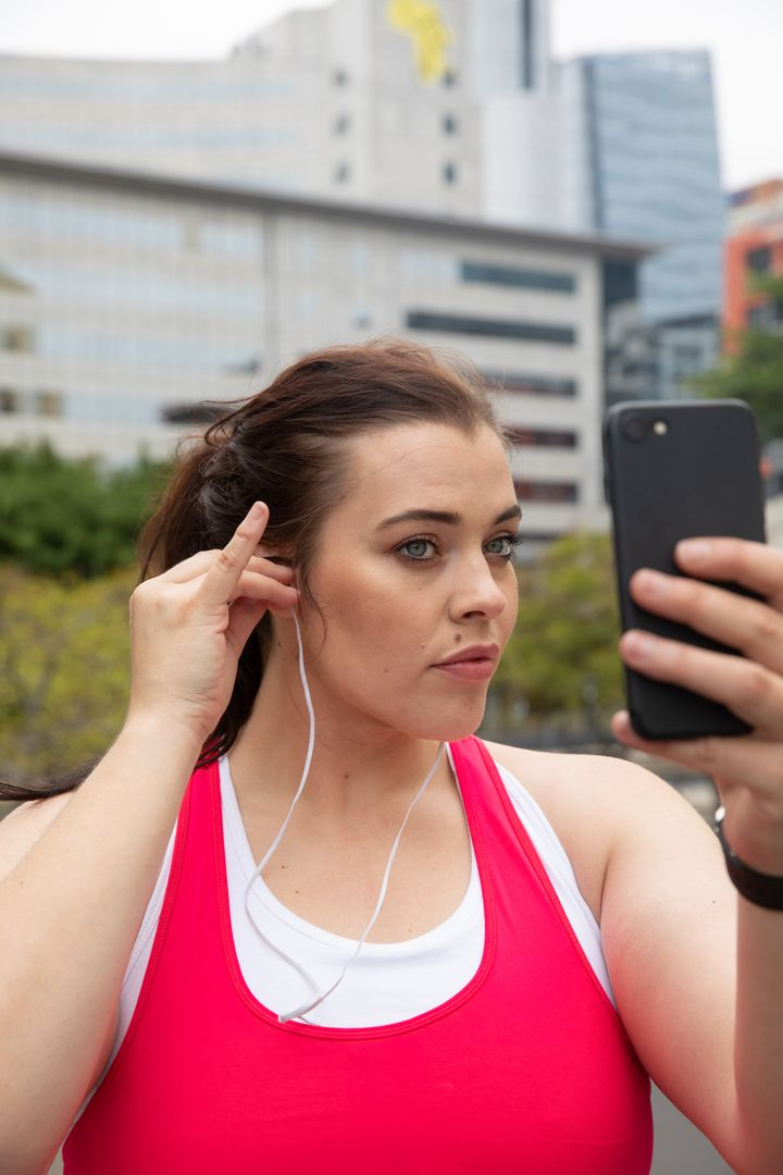 Attractive curvy Caucasian woman with long dark hair wearing sports clothes exercising in a city, using her smartphone and putting earphones on, with modern buildings in the background Free Stock Images from PikWizard