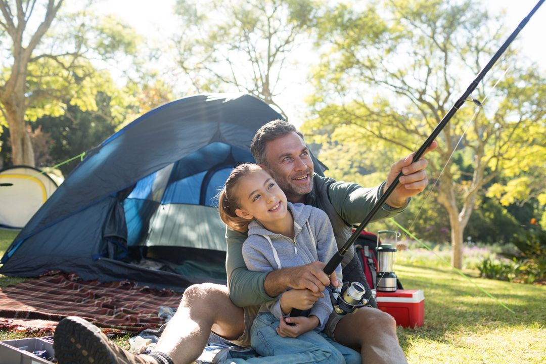 Father and daughter holding a fishing rod outside the tent while fly fishing Free Stock Images from PikWizard