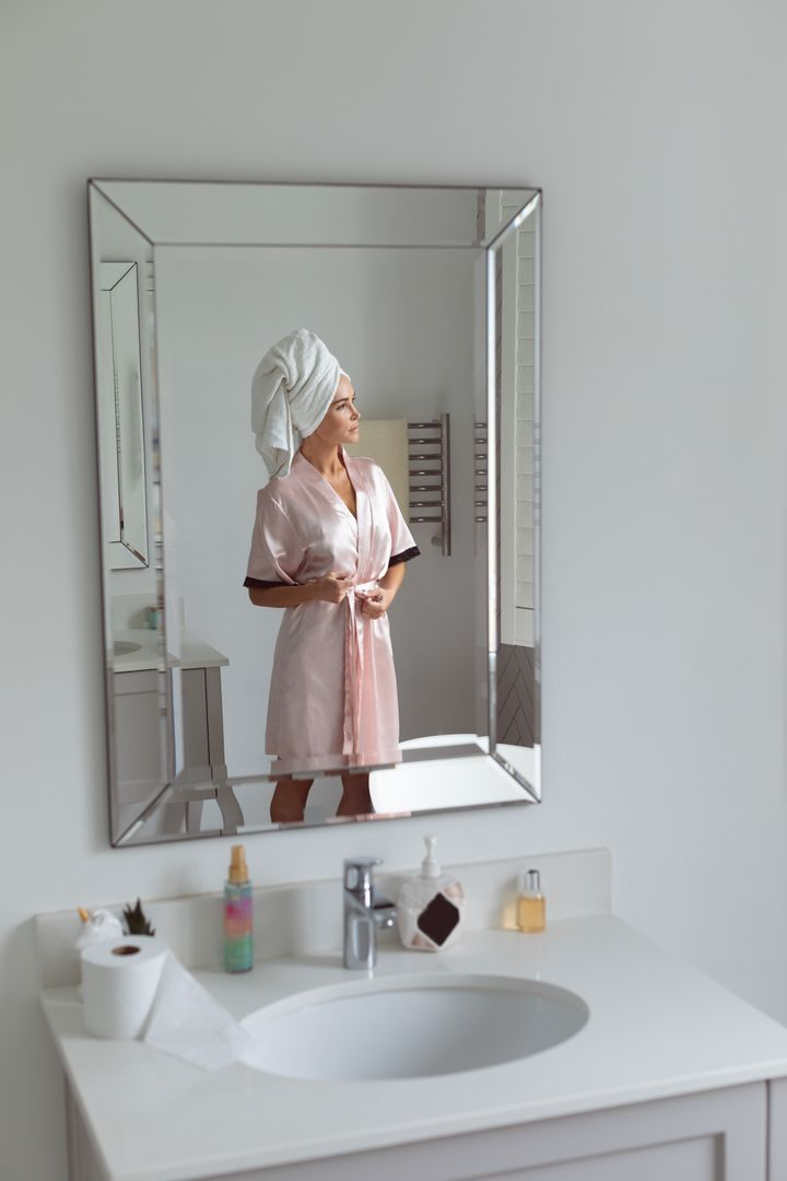 Reflection of woman in mirror tying knot of nightwear in bathroom at home