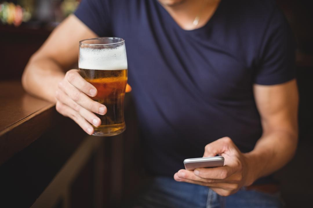 Mid section of man using mobile phone while having glass of beer in bar