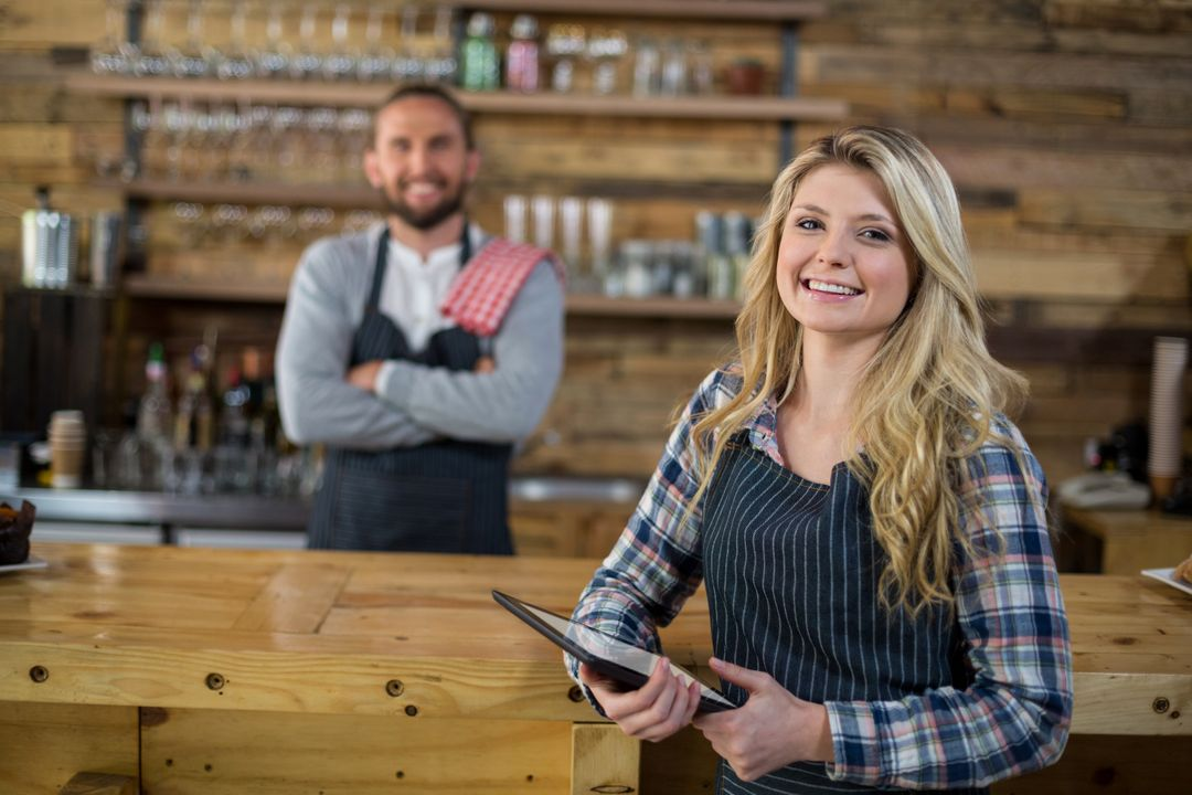 Portrait of smiling waitress standing with digital tablet in café Free Stock Images from PikWizard