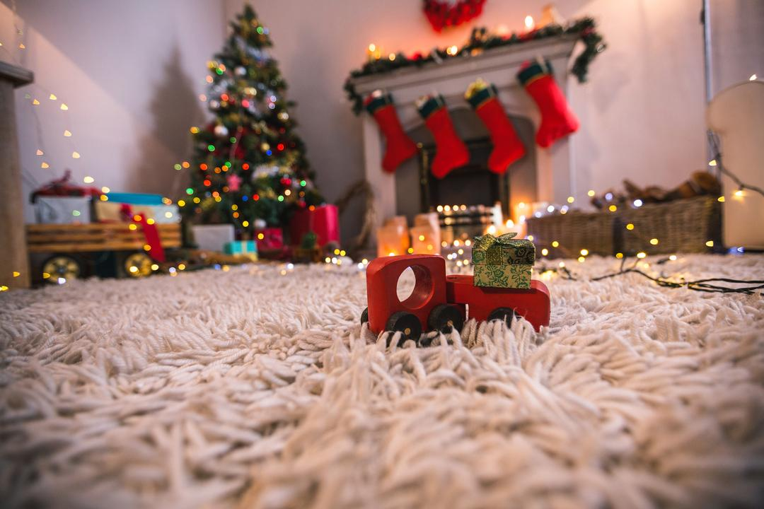 Toy car carrying christmas gift box on fur carpet