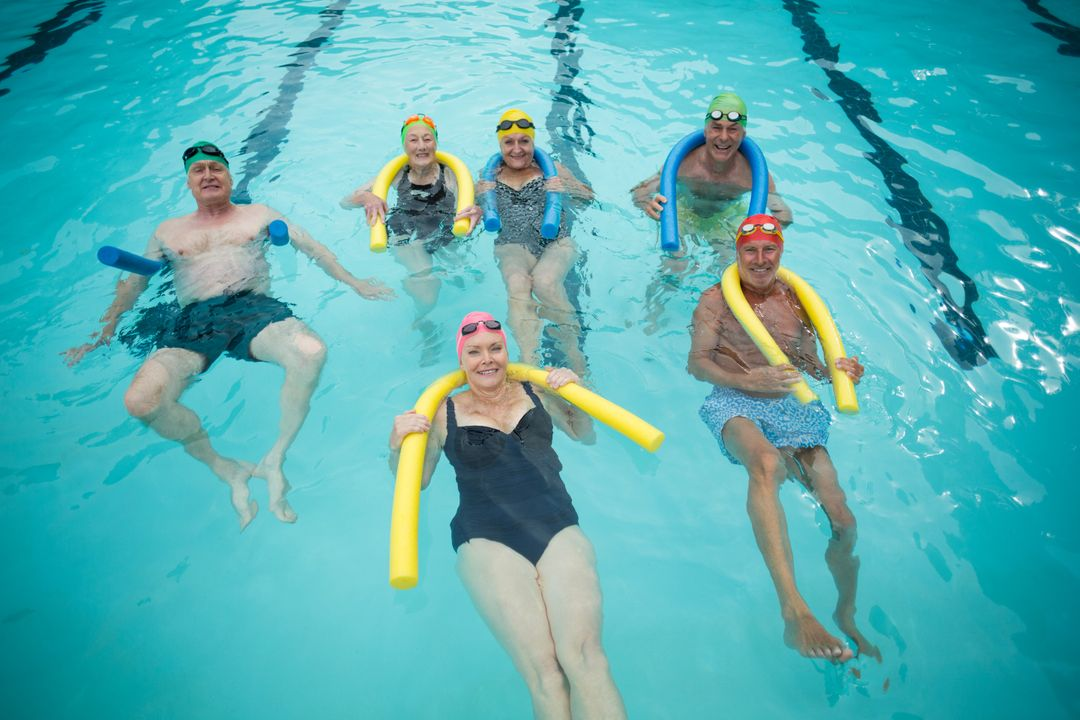 Group of swimmers swimming with pool noodles