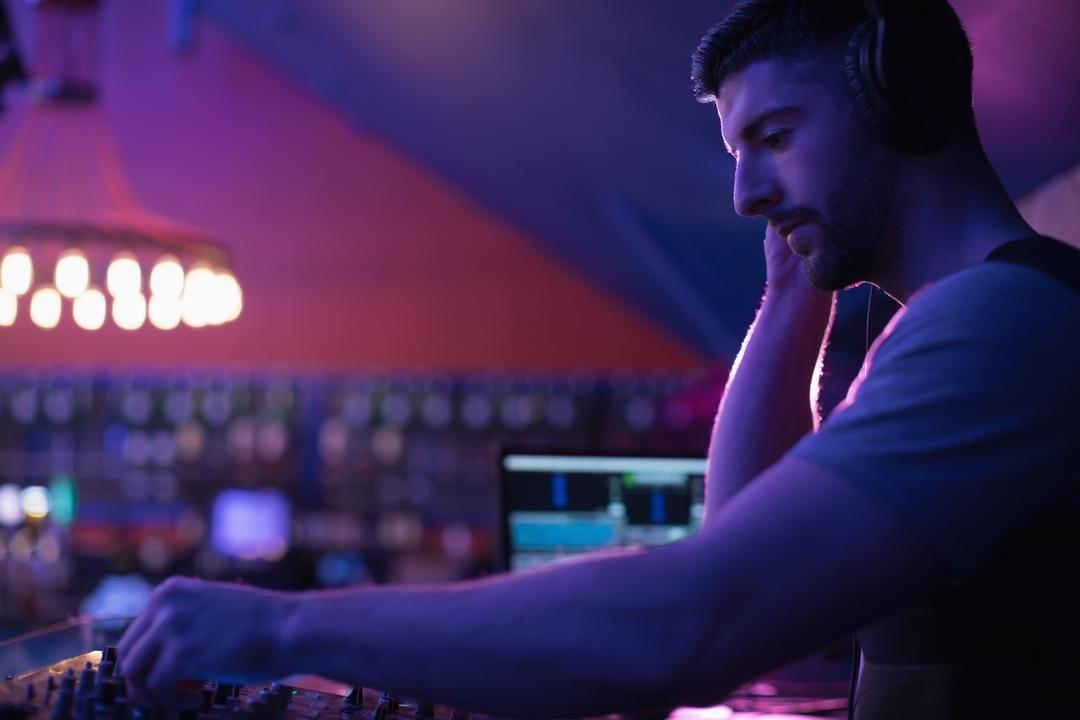 Male dj listening to headphones while playing music in bar Free Stock Images from PikWizard