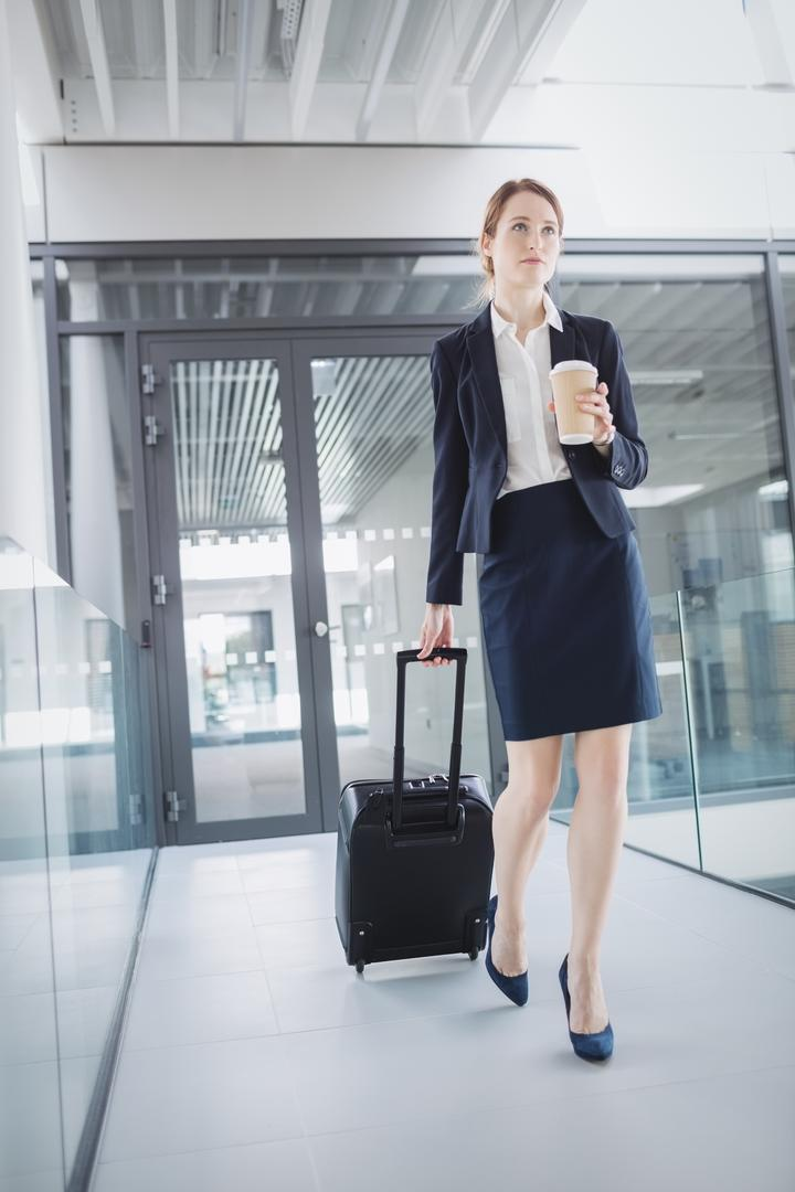 Businesswoman holding suitcase walking through office corridor