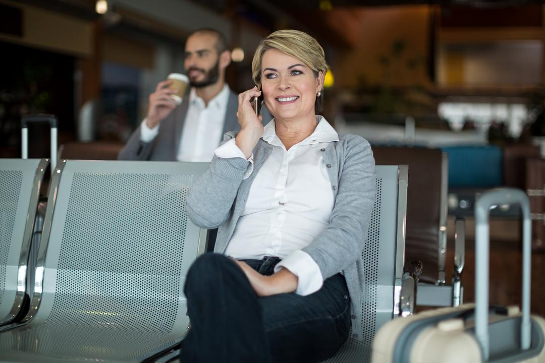 Smiling businesswoman talking on mobile phone in waiting area at airport terminal