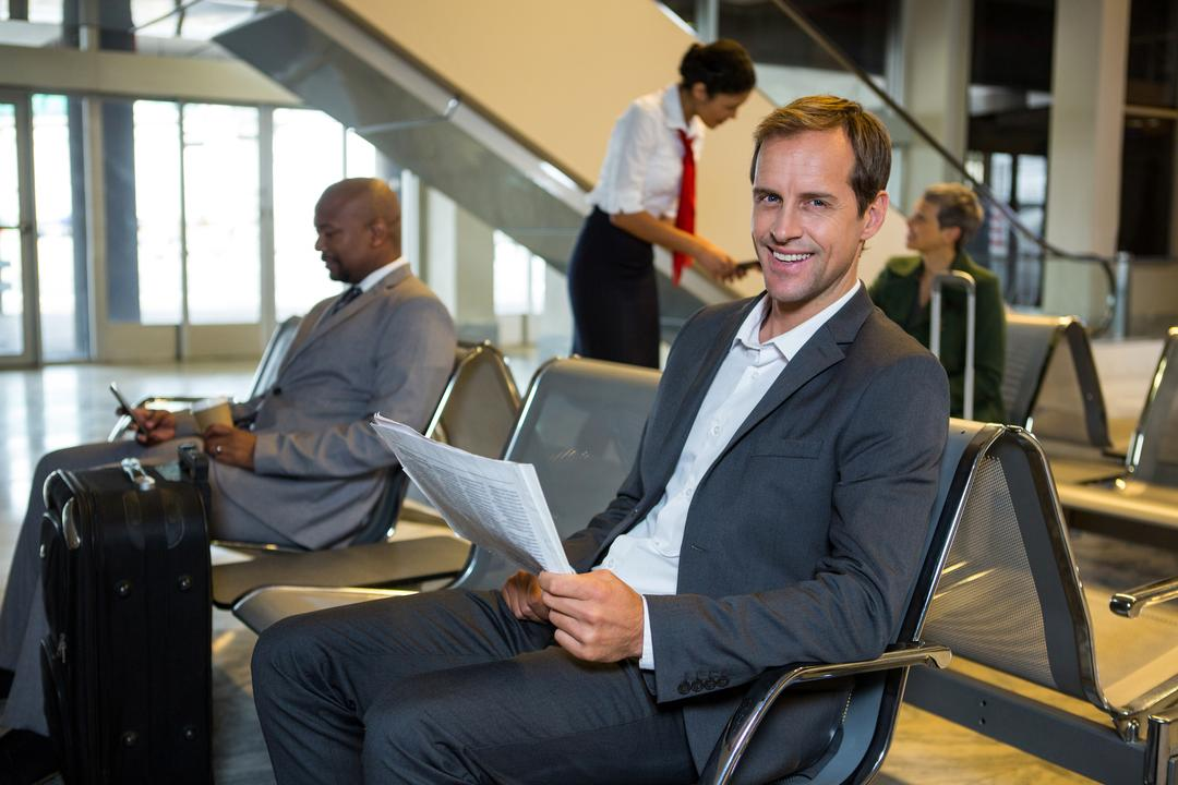 Portrait of businessman reading newspaper in waiting area at airport Free Stock Images from PikWizard
