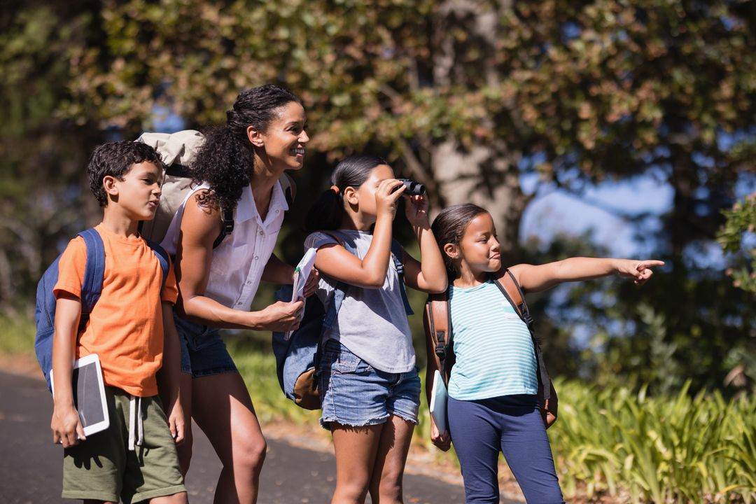 Girl pointing away with friends and teacher on street during summer field trip