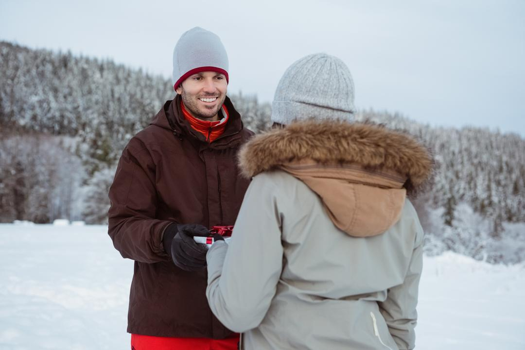 Woman giving gift to smiling man on snow covered mountain