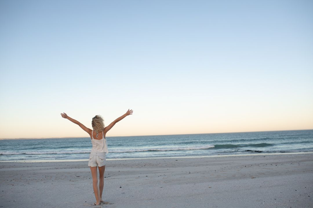 Rear view of woman standing with arms outstretched on the beach