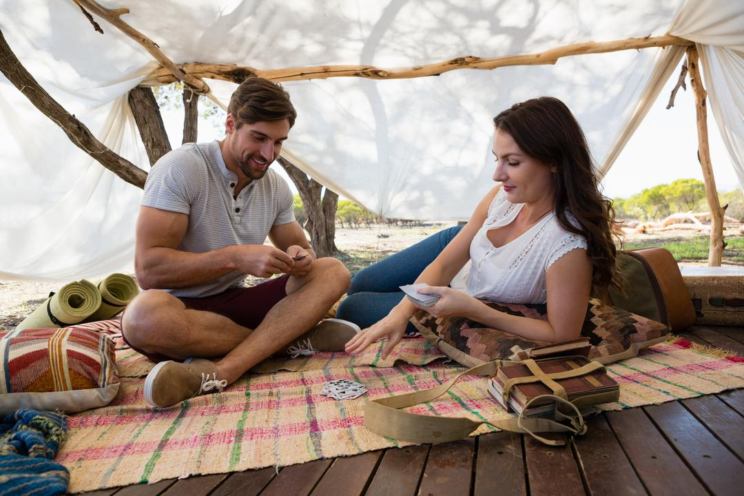 Relaxed couple playing cards on plank in tent