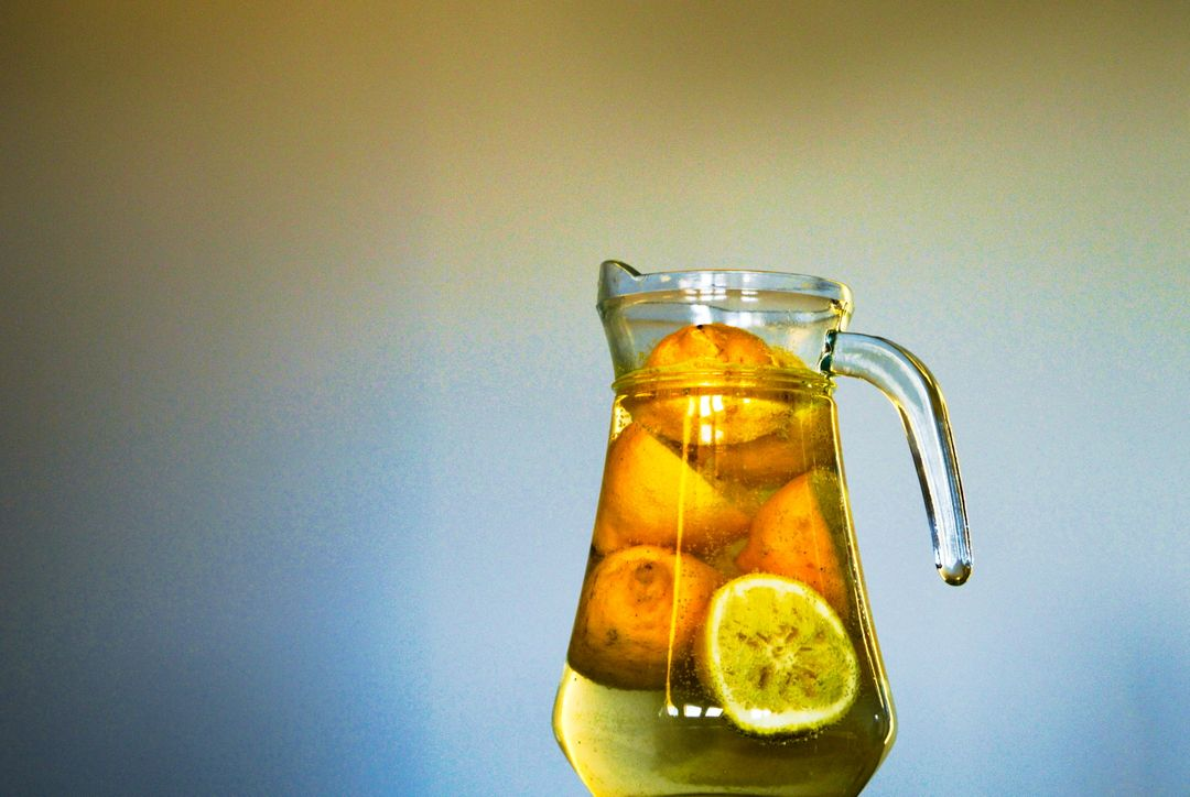 Clear Glass Pitcher With Sliced Yellow Round Fruit Inside