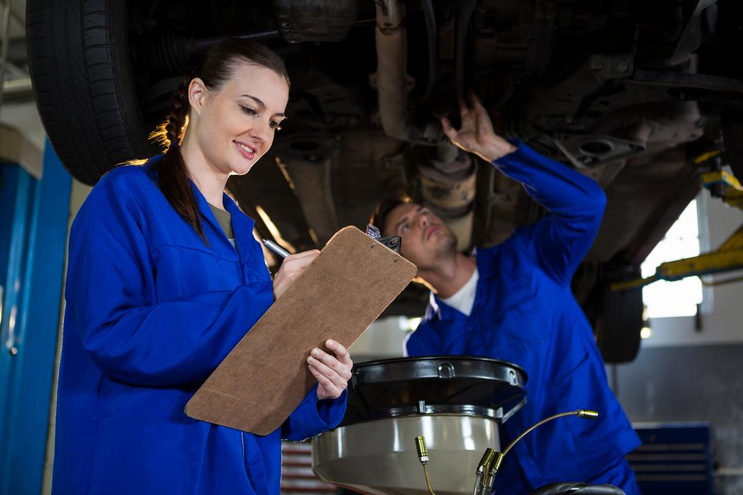 Mechanics preparing a check list while his colleague examining a car engine in the background