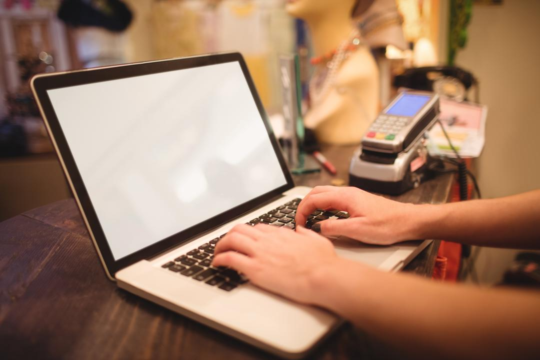Hands of female staff using laptop at a counter in boutique store