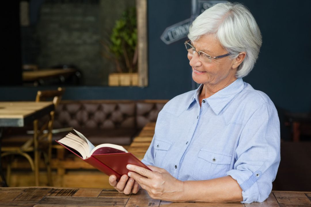 Smiling senior woman reading book while sitting by table at cafe shop Free Stock Images from PikWizard