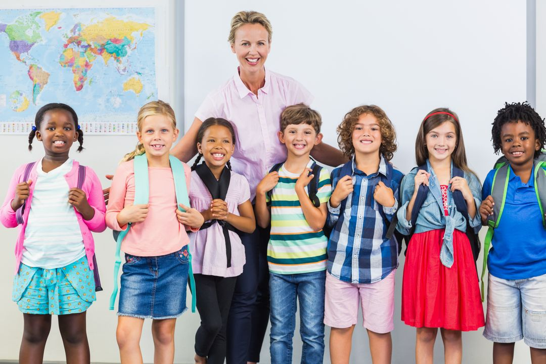 Portrait of smiling teacher and kids standing together with arm around in classroom at school