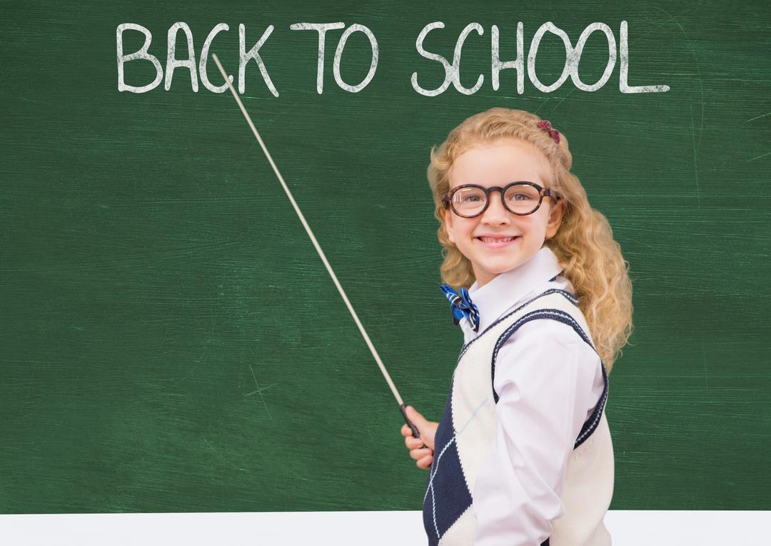 Smiling girl with stick pointing at back to school on green board