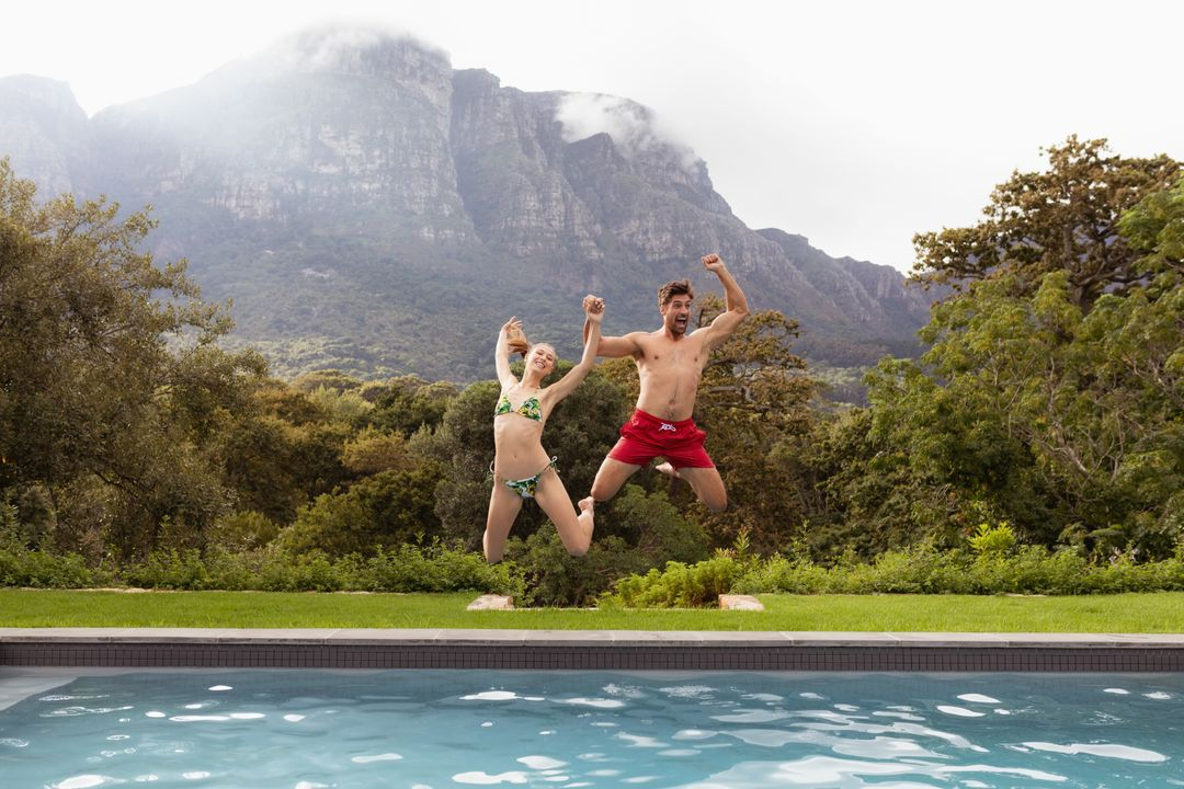 Couple jumping together in the swimming pool at backyard Free Stock Images from PikWizard