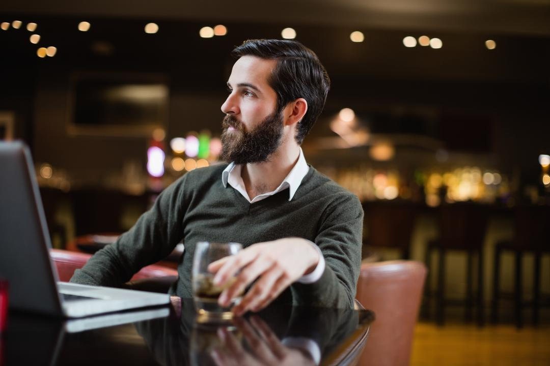 Man with glass of drink and laptop on table in bar