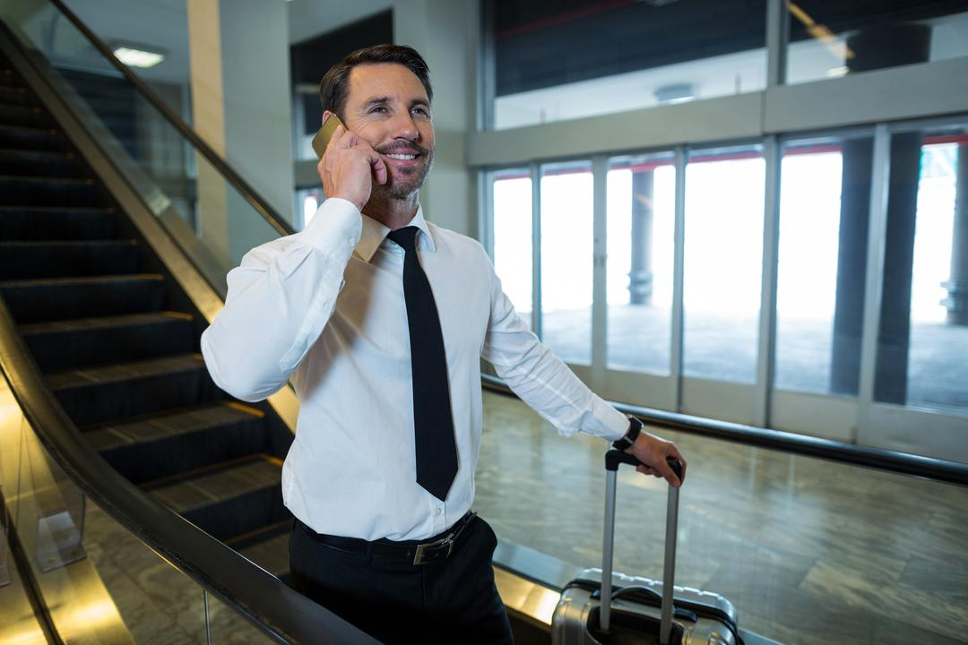 Businessman on escalator talking on mobile phone in airport