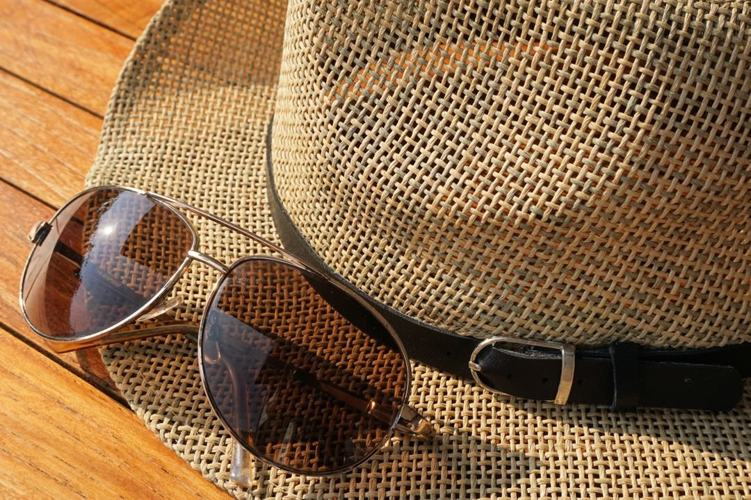 Brown Strawhat Beside Brown Aviator Sunglasses