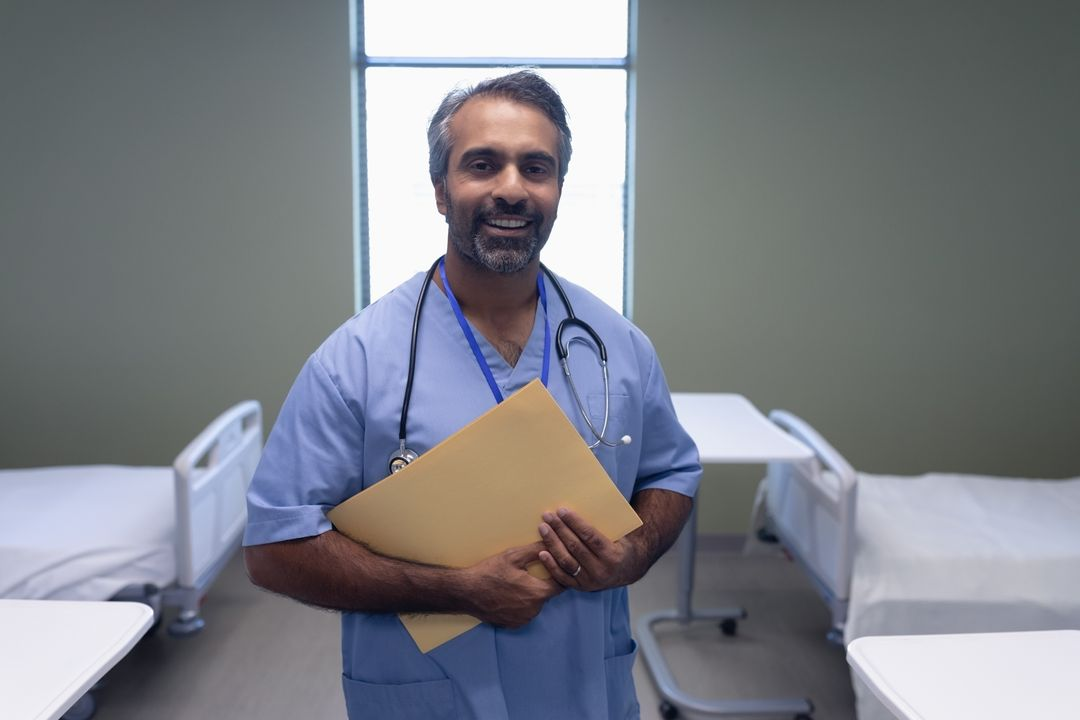 Portrait of mixed race male doctor holding medical file in the ward at hospital