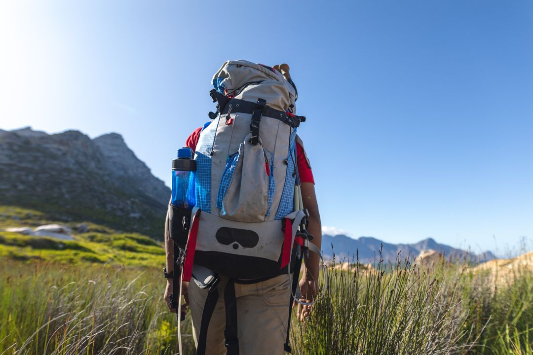 Rear view of fit, disabled mixed race male athlete with prosthetic leg, enjoying his time on a trip to the mountains, hiking in field with backpack. Active lifestyle with disability. Free Stock Images from PikWizard